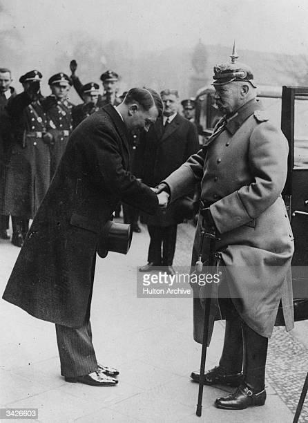 German dictator Adolf Hitler bows as he shakes hands with Paul von Hindenburg in the Unter den Linden Berlin