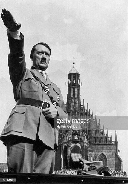 German dictator Adolf Hitler giving the Nazi salute from his car whilst at the Nazi Party Congress