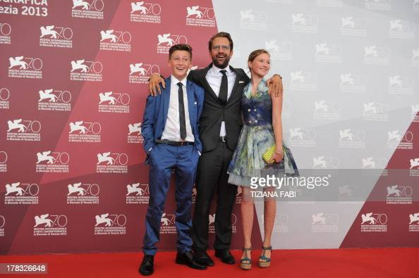 German director Rick Ostermann poses with actors Levin Liam and actress Helena Phil during the photocall of Wolfskinder presented in the Orizzonti...
