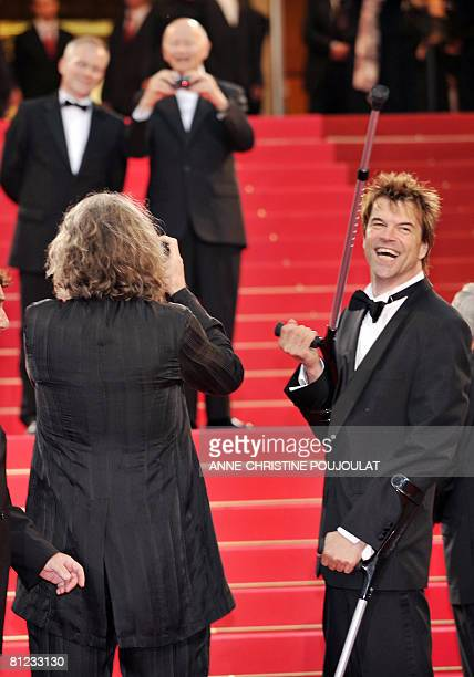 German director Wim Wenders takes photos as German actor and singer Campino plays with his crutch as they arrive to attend the screening of their...