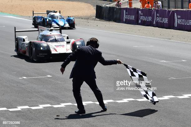 TOPSHOT German driver Timo Bernhard crosses the finish line onboard his Porsche 919 Hybrid N°2 to win the 85th Le Mans 24hours endurance race on June...