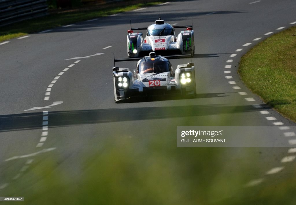 German driver Timo Bernhard in his Porsche 919 Hybrid N° 20 (L) and German driver Andre Lotterer in his Audi R18 E-Tron Quattro Hybrid N°2 (R) compete during the 82nd Le Mans 24 hours endurance race, on June 15, 2014 in Le Mans, western France. Fifty-six cars with 168 drivers are participating on June 14 and 15 in the Le Mans 24-hours endurance race.