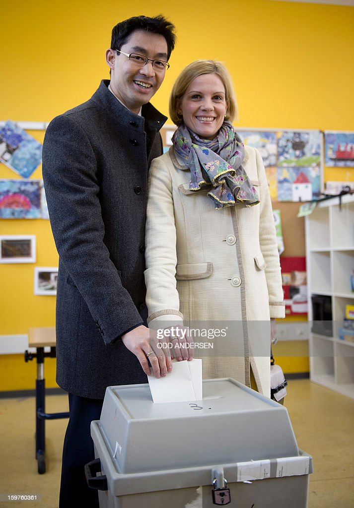 German Economy Minister and Chairman of the German liberal party (FDP), Phillip Roesler and his wife Wibke cast their ballots at a polling station at the Friedrich-Dierks Schule in Isernhagen on January 20, 2013 on polling day of the local elections in the central German state of Lower Saxony. The vote is largely seen as a test run for autumn's federal election.