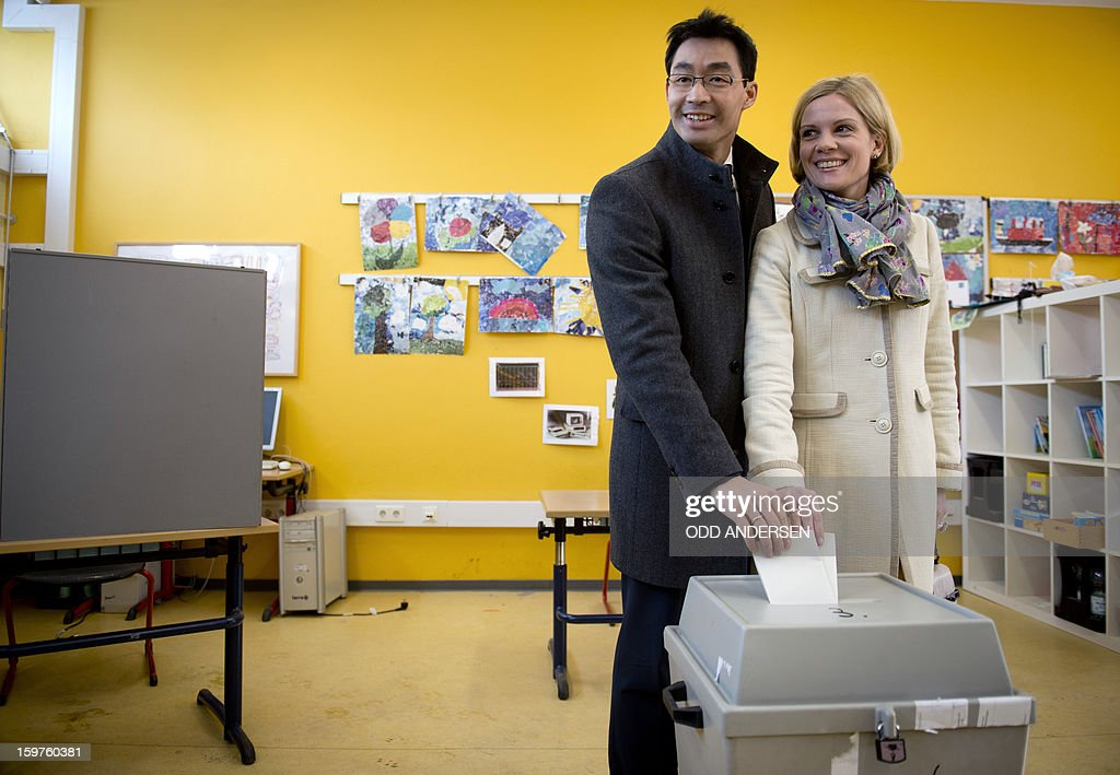 German Economy Minister and Chairman of the German liberal party (FDP), Phillip Roesler and his wife Wibke cast their ballots at a polling station at the Friedrich-Dierks Schule in Isernhagen on January 20, 2013 on polling day of the local elections in the central German state of Lower Saxony. The vote is largely seen as a test run for autumn's federal election. AFP PHOTO / ODD ANDERSEN