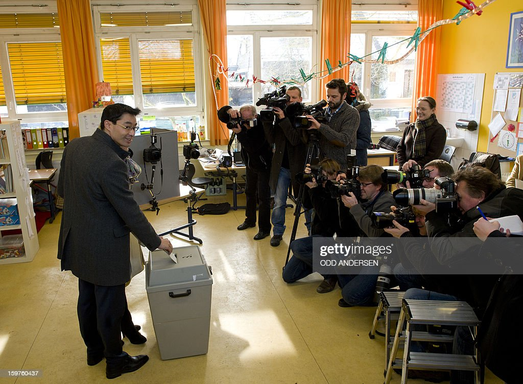 German Economy Minister and Chairman of the German liberal party (FDP), Phillip Roesler (L) casts his ballot at a polling station at the Friedrich-Dierks Schule in Isernhagen on January 20, 2013 on polling day of the local elections in the central German state of Lower Saxony. The vote is largely seen as a test run for autumn's federal election.