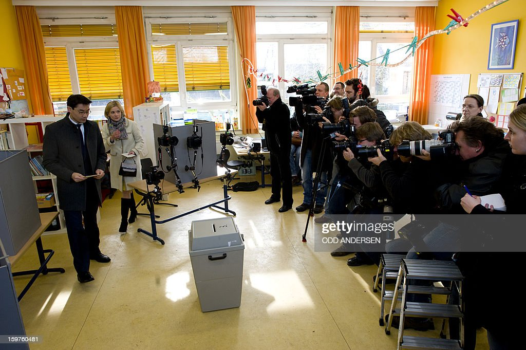 German Economy Minister and Chairman of the German liberal party (FDP), Phillip Roesler (L) and his wife Wibke cast their ballots at a polling station at the Friedrich-Dierks Schule in Isernhagen as photographers take pictures on January 20, 2013 on polling day of the local elections in the central German state of Lower Saxony. The vote is largely seen as a test run for autumn's federal election.