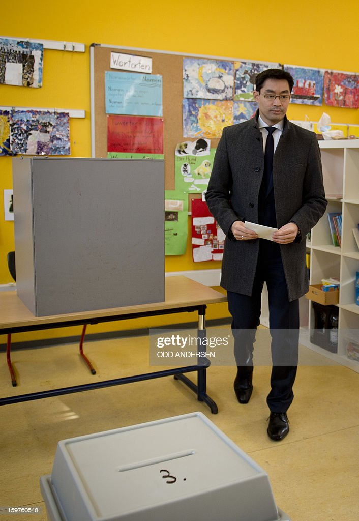 German Economy Minister and Chairman of the German liberal party (FDP), Phillip Roesler holds his ballot at a polling station at the Friedrich-Dierks Schule in Isernhagen on January 20, 2013 on polling day of the local elections in the central German state of Lower Saxony. The vote is largely seen as a test run for autumn's federal election.