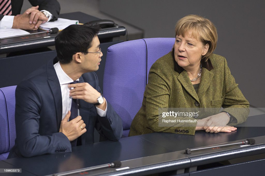 German Economy Minister and Vice Chancellor Philipp Roesler (L) and German Chancellor <a gi-track='captionPersonalityLinkClicked' href=/galleries/search?phrase=Angela+Merkel&family=editorial&specificpeople=202161 ng-click='$event.stopPropagation()'>Angela Merkel</a> (R) arrive at the Reichstag, the seat of the German Parliament (Bundestag), on January 17, 2013 in Berlin, Germany. Roesler warned that a short-term deal with the euro crisis through inflation, stating that it's not 'A price we are not willing to pay - the price of monetary stability' in his inaugural speech to the annual economic report in parliament. Merkel's Christian Democratic Union (CDU) will face an electoral test this Sunday as voters go to the polls in Lower Saxony.