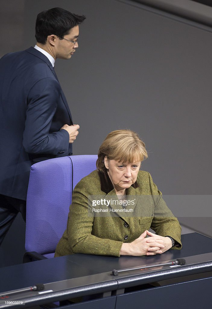 German Economy Minister and Vice Chancellor Philipp Roesler (L) and German Chancellor <a gi-track='captionPersonalityLinkClicked' href=/galleries/search?phrase=Angela+Merkel&family=editorial&specificpeople=202161 ng-click='$event.stopPropagation()'>Angela Merkel</a> (R) arrives at the Reichstag, the seat of the German Parliament (Bundestag), on January 17, 2013 in Berlin, Germany. Roesler warned that a short-term deal with the euro crisis through inflation, stating that it's not 'A price we are not willing to pay - the price of monetary stability' in his inaugural speech to the annual economic report in parliament. Merkel's Christian Democratic Union (CDU) will face an electoral test this Sunday as voters go to the polls in Lower Saxony.