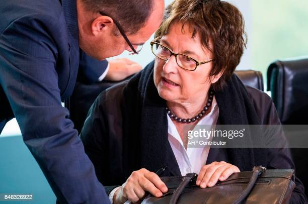 German economy minister Brigitte Zypries speaks with an unidentified aide prior to the weekly cabinet meeting at the Chancellery in Berlin on...