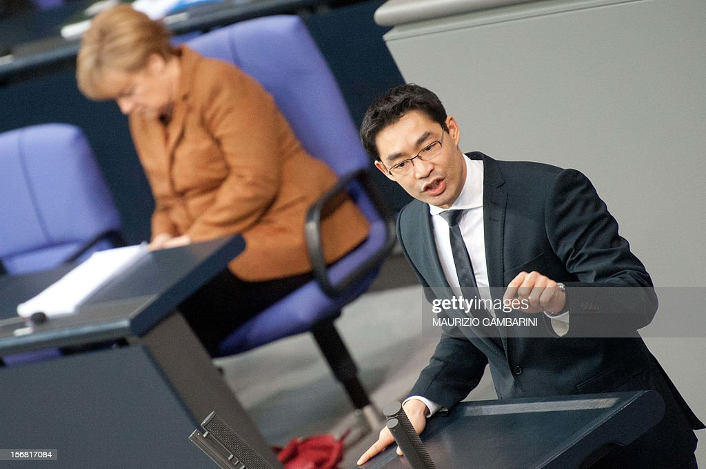 German Economy Minister Philipp Roesler delivers a speech as German Chancellor Angela Merkel listens on November 22, 2012 at Bundestag in Berlin. If the upper house of the German parliament on Friday votes down a deal on the taxation of German assets parked in Swiss bank accounts it would mean 'lost money for the German state,' the head of the Swiss Bankers' Association Claude-Alain Margelisch told reporters in Geneva. AFP PHOTO / Maurizio Gambarini/ GERMANY OUT