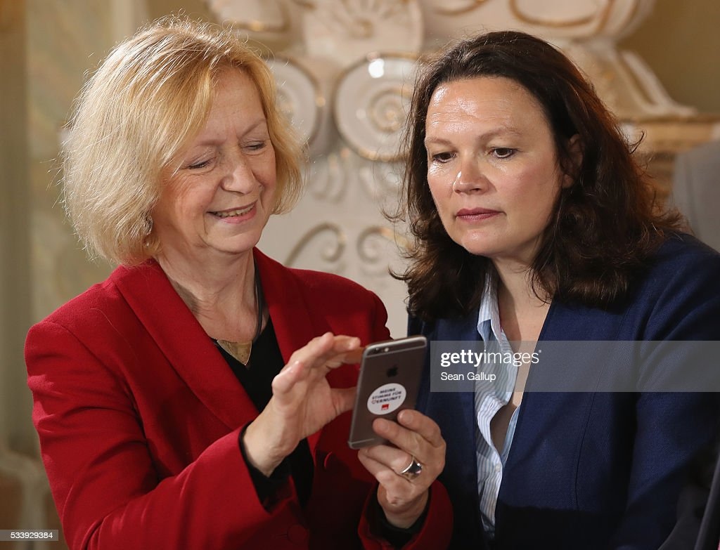 German Education Minister <a gi-track='captionPersonalityLinkClicked' href=/galleries/search?phrase=Johanna+Wanka&family=editorial&specificpeople=5626570 ng-click='$event.stopPropagation()'>Johanna Wanka</a> (L) and Minister of Work and Social Issues <a gi-track='captionPersonalityLinkClicked' href=/galleries/search?phrase=Andrea+Nahles&family=editorial&specificpeople=822618 ng-click='$event.stopPropagation()'>Andrea Nahles</a> look at something on the mobile phone of Vice Chancellor and Economy and Energy Minister Sigmar Gabriel at a meeting of the German government cabinet at Schloss Meseberg palace on May 24, 2016 in Gransee, Germany. The government cabinet is meeting at Schloss Meseberg for a two-day retreat.