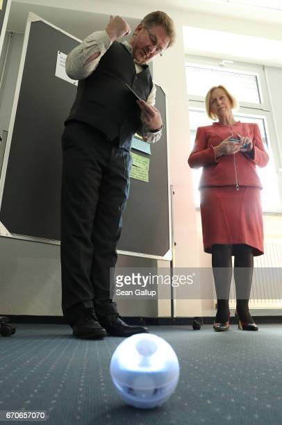 German Education Minister Johanna Wanka looks on as instructor Carsten Busch explains the use of digital tools such as a program on a tablet and a...