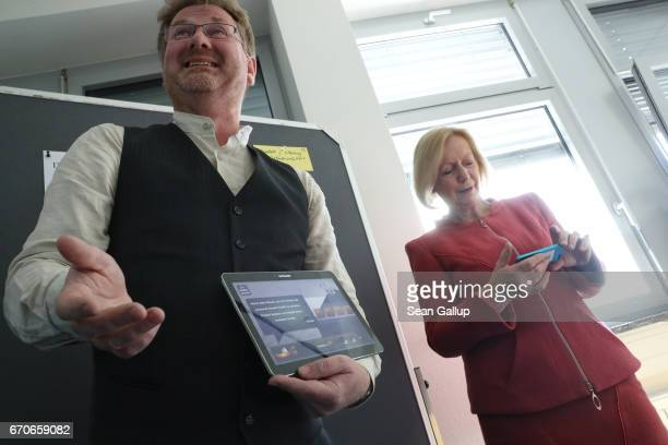 German Education Minister Johanna Wanka looks on as instructor Carsten Busch explains the use of digital tools such as a program on a tablet during a...