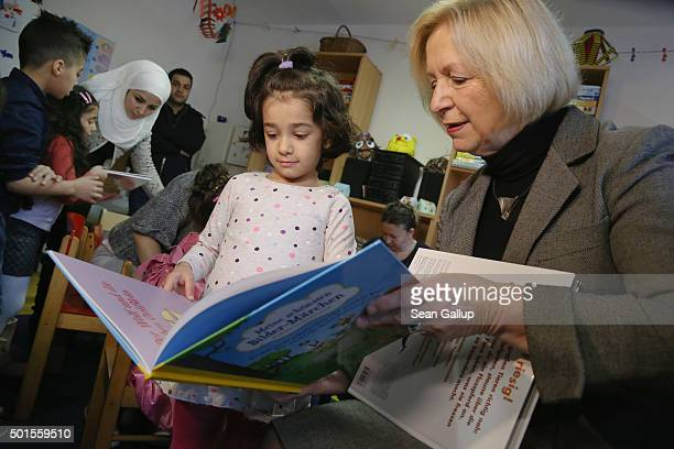 German Education Minister Johanna Wanka shares a book with Sahra from Afghanistan during the presentation of a new initiative to help children of...