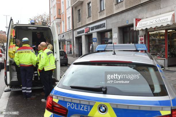 German emergency personnel stand next to their vehicle inside a security perimeter that was set after a man attacked passersby near Rosenheimer...