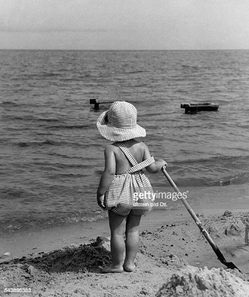 a little girl with a shovel at the beach Photographer Atelier Binder Published by 'Die Gruene Post' 33/1937Vintage property of ullstein bild