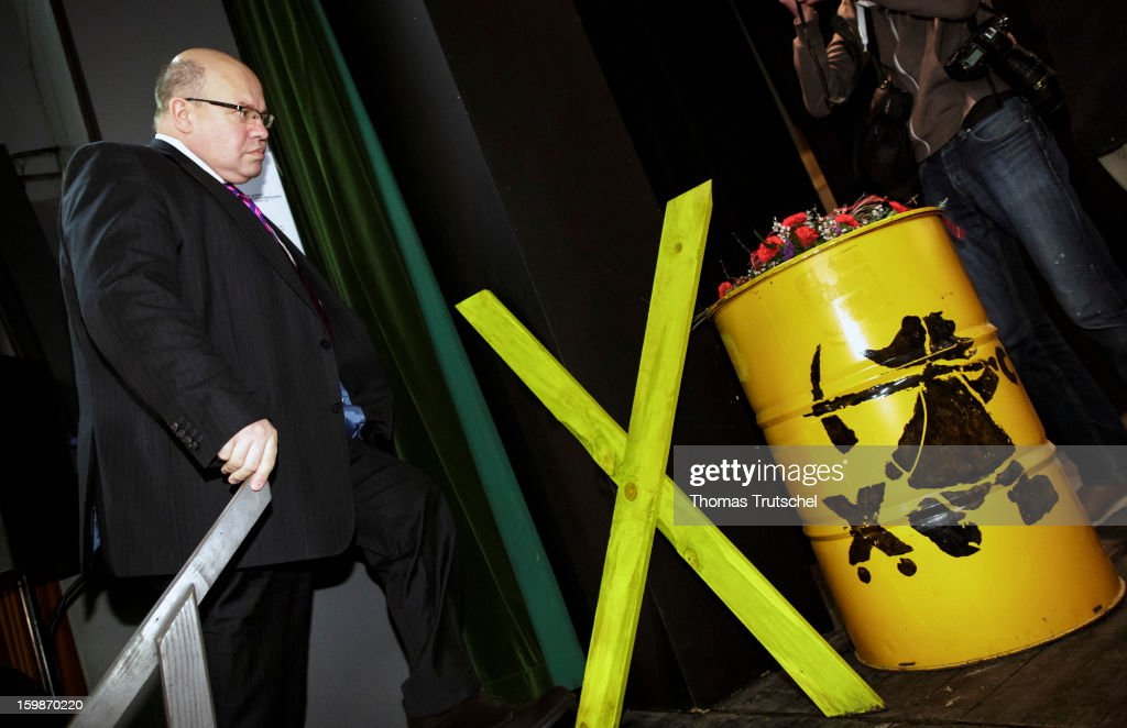 German Environment Minister Peter Altmaier walks past a nuclear waste barrel at Gildehaus on January 21, 2013 in Luechow. Altmaier met people from the Wendland region in Lower Saxony to discus the problems of storing nuclear waste in Gorleben.