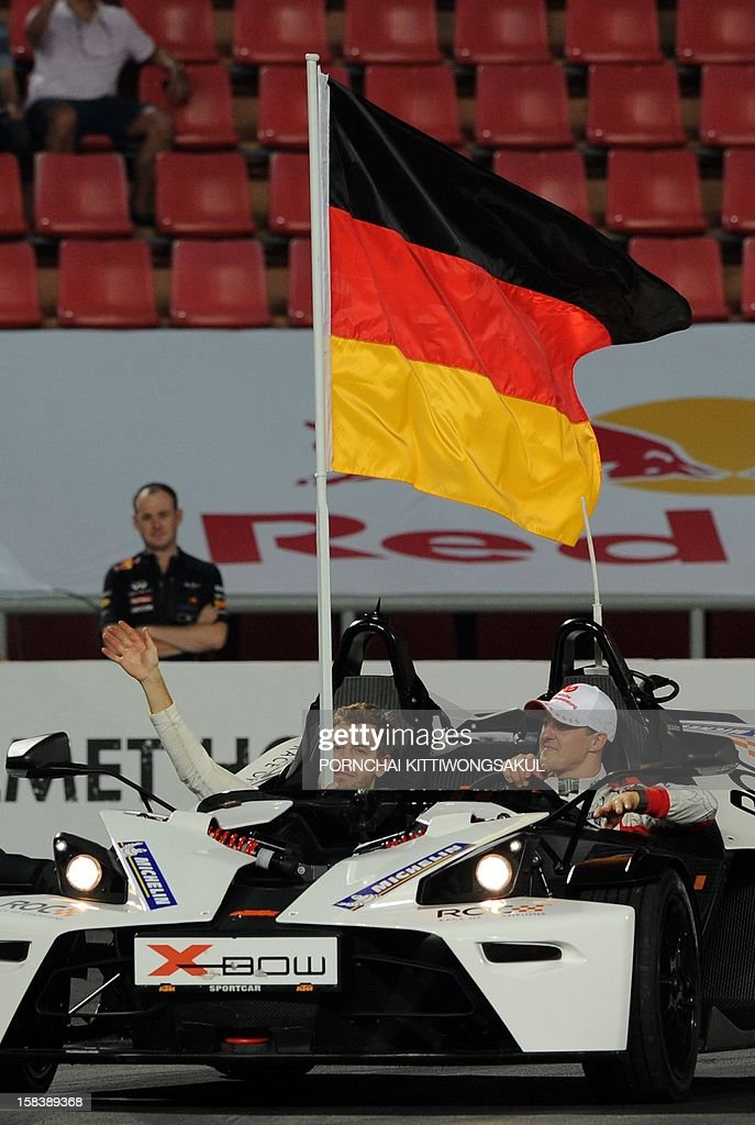 German F1 driver and seven times World champion Michael Schumacher (R) sits next to Formula One World Champion Sebastian Vettel (L) during the Race of Champions (ROC) Nations Cup Drivers 's Presentation at Rajamangala Stadium in Bangkok on December 15, 2012. The Race of Champions (ROC) will take place in Thailand between December 14 and 16 and brings together heavyweights from all motor racing disciplines in the same type of car.