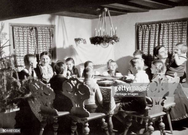 German family at Christmas Germany 1936 A picture showing many children and their mother eating round a table A portrait depicting happy home life...