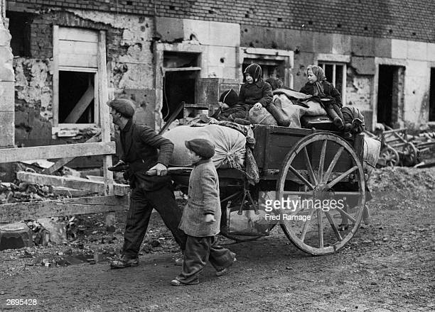 A German family in Munchen Gladbach being taken to a shelter on a handcart pulled by their father following the advance by the US Ninth Army