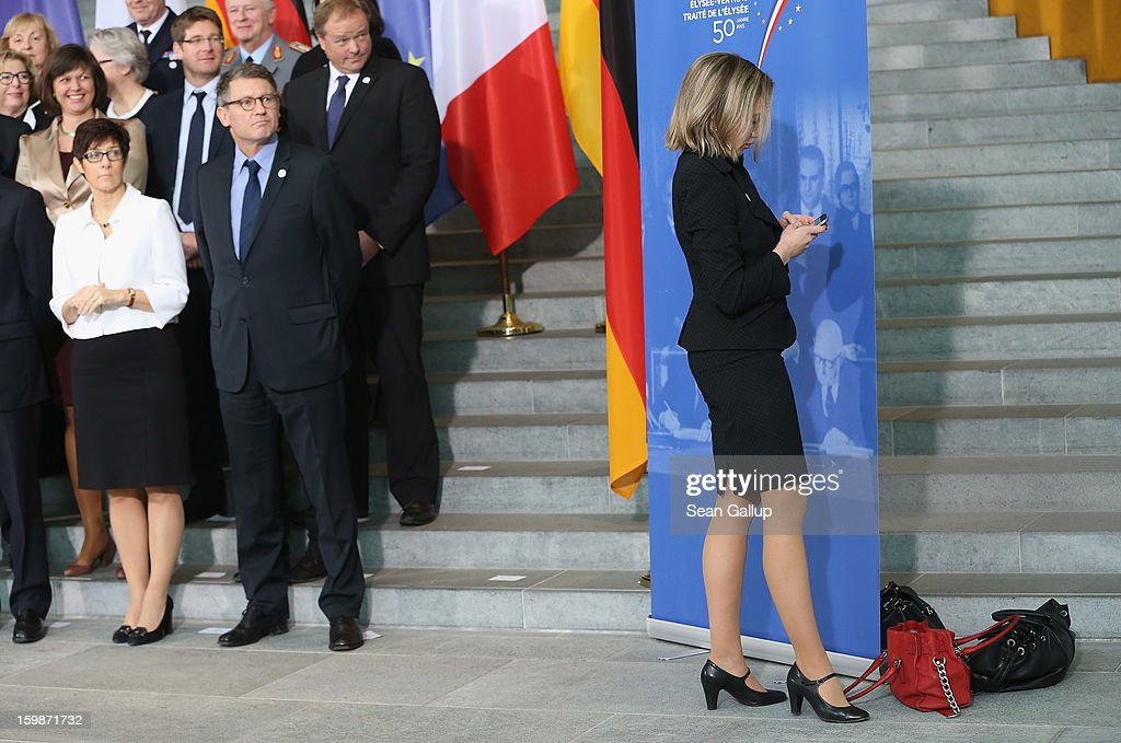 German Family Minister Kristina Schroeder checks her mobile phone next to handbags left by her and other female government ministers prior to a group photo of the French and German government members at the Chancellery during the 50th anniversary celebration of the Elysee Treaty on January 22, 2013 in Berlin, Germany. The treaty, concluded in 1963 by Charles de Gaulle and Konrad Adenauer in the Elysee Palace in Paris, set a new tone of reconciliation between France and Germany, and called for consultations between the two countries to come to a common stance on policies affecting the most important partners in Europe as well as the rest of the region. Since its establishment, the document for improved bilateral relations has been seen by many as the driving force behind European integration.