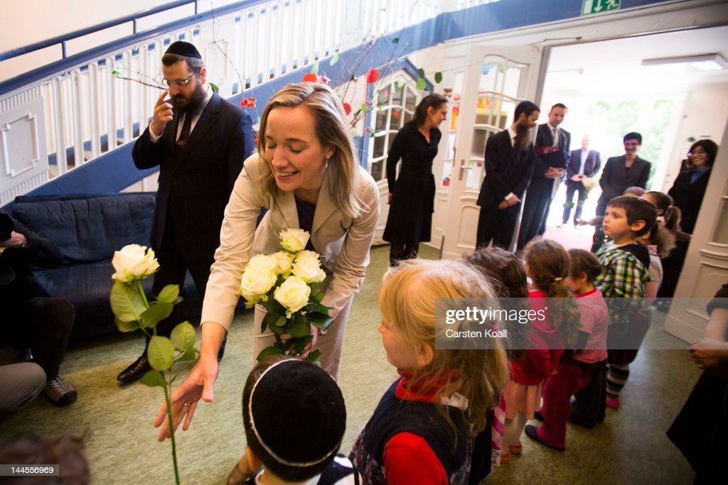 German Family Minister Kristina Schroeder (C) gets a white rose as she visits the Gan Israel Jewish kindergarten on May 16, 2012 in Berlin, Germany. Berlin has a fast-growing Jewish population, much of which is due to an influx of Jewish immigrants from Russia and the former Soviet Union.