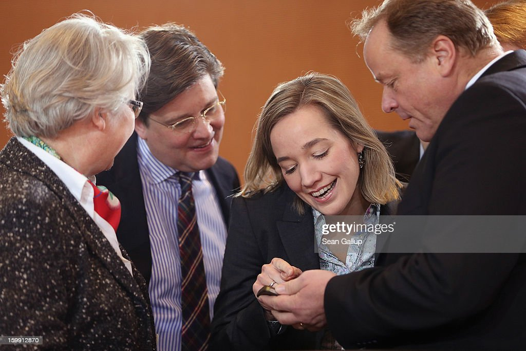 German Family Minister Kristina Schroeder (3rd from L) looks at a display on the phone of Development Minister <a gi-track='captionPersonalityLinkClicked' href=/galleries/search?phrase=Dirk+Niebel&family=editorial&specificpeople=710721 ng-click='$event.stopPropagation()'>Dirk Niebel</a> (R) as Education Minister <a gi-track='captionPersonalityLinkClicked' href=/galleries/search?phrase=Annette+Schavan&family=editorial&specificpeople=599358 ng-click='$event.stopPropagation()'>Annette Schavan</a> (L) and Chancellery State Secretary Eckart von Klaeden look on at the weekly German government cabinet meeting on January 23, 2013 in Berlin, Germany. High on the morning's agenda was the 2012 government report on skilled labour in Germany.