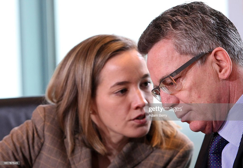 German Family Minister Kristina Schroeder (L) speaks to German Defense Minister <a gi-track='captionPersonalityLinkClicked' href=/galleries/search?phrase=Thomas+de+Maiziere&family=editorial&specificpeople=618845 ng-click='$event.stopPropagation()'>Thomas de Maiziere</a> as they arrive for the weekly German federal cabinet meeting on February 27, 2013 in Berlin, Germany. High on the morning's agenda was discussion of the country's annual report on disarmament as well as of potential modifications to a law on employment rights for foreigners.