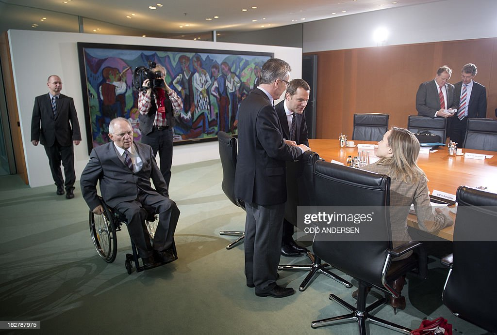 German family minister Kristina Schroeder (seated, R) speaks with defence minister Thomas de Maiziere (centre, L) and health minister Daniel Bahr (centre, R) as German finance minster Wolfgang Schaeuble (L) arrives for the weekly cabinet meeting at the Chancellery in Berlin on February 27, 2013.