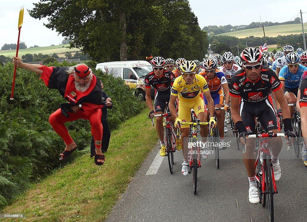 German fan Didi Senft known as El Diablo jumps as overall leader Spanish Alejandro Valverde rides in the pack on July 6 2008 in SaintBrieuc western...