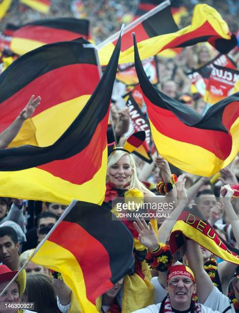 German fans hold national flags on June 13 2012 near the Brandenburg Gate in Berlin at the beginning of the screening of the Euro 2012 championships...