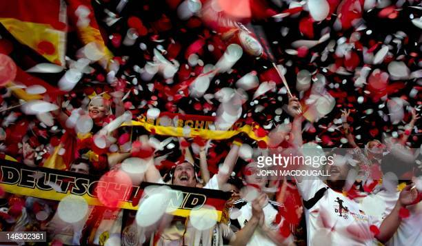 German fans hold national flags while celebrating on June 13 2012 near the Brandenburg Gate in Berlin at the end of the screening of the Euro 2012...