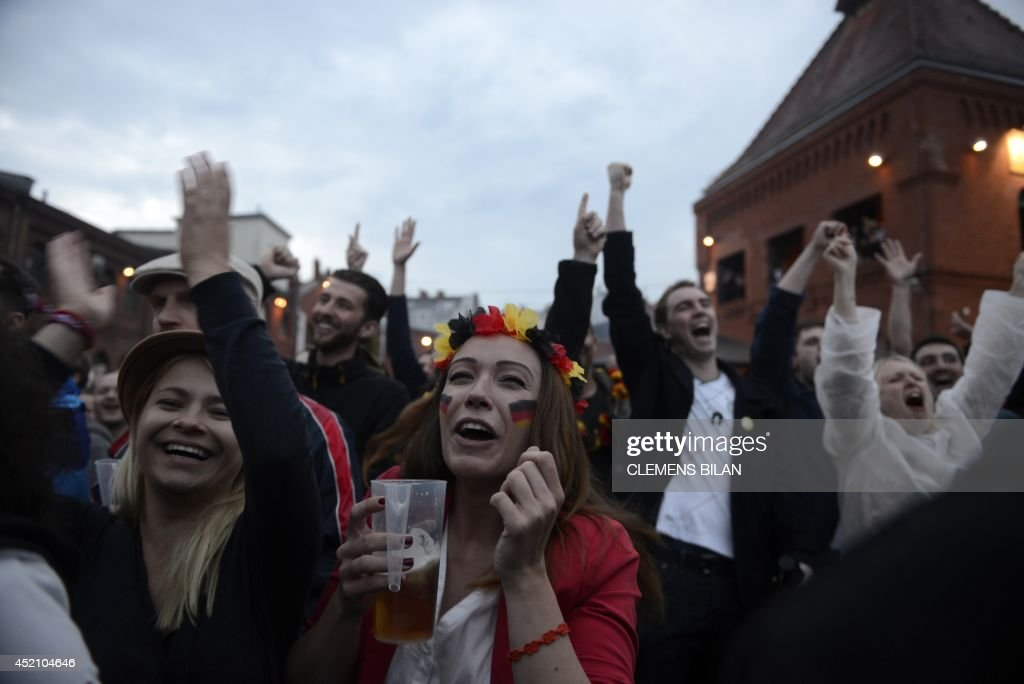 German fans react and hold a cup of beer in the courtyard of the Kulturbrauerei (Culture Brewery) in Berlin on July 13, 2014 in front of a giant screen displaying the FIFA World Cup 2014 final football match Germany vs Argentina played in Brazil.