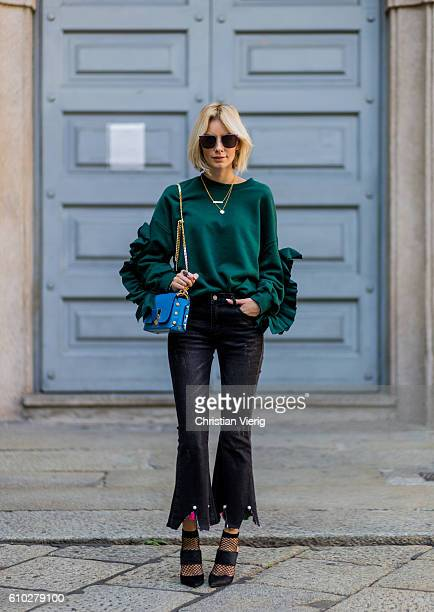 German fashion blogger Lisa Hahnbueck wearing green Storets Oversized Sweatshirt with Ruffle Sleeves dark black Storets Cropped Flare Jeans with...