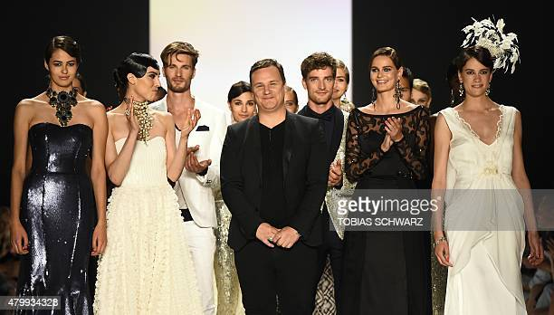 German fashion designer Guido Maria Kretschmer reacts next to models who presented his works during the Berlin Fashion Week SpringSummer 2016 in...