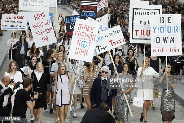 German fashion designer Karl Lagerfeld acknowledges the public as Brazilian model Gisele Bundchen speaks through a megaphone as she and other models...