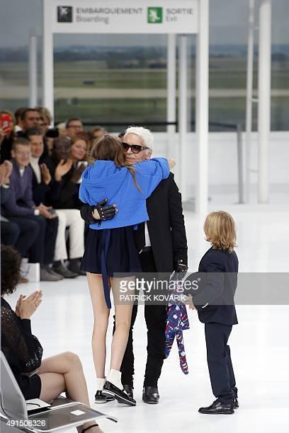 German fashion designer Karl Lagerfeld embraces British model Cara Delevingne next to his godson Hudson Kroenig during the Chanel 2016 Spring/Summer...