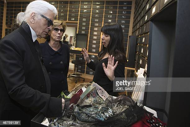 German fashion designer Karl Lagerfeld looks at fabric samples during a visit to one of the workshops that work for Chanel in Pantin outside of Paris...
