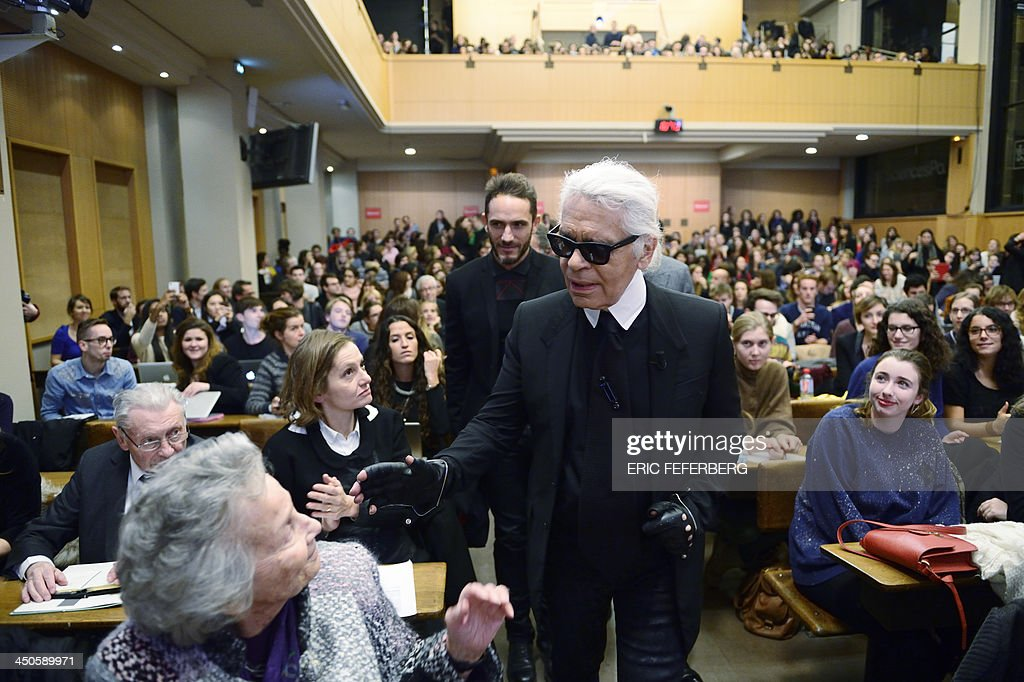 German fashion designer Karl Lagerfeld (C) meets Eliane Heilbronn, mother of the main Chanel shareholder, at the Institute of Political Studies (IEP) or 'Sciences Po' before giving a master class on November 19, 2013 in Paris.