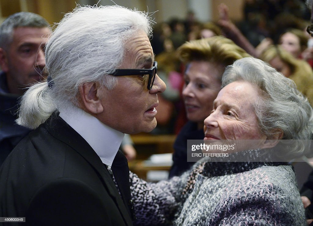German fashion designer Karl Lagerfeld (L) meets Eliane Heilbronn, mother of the main Chanel shareholder, at the Institute of Political Studies (IEP) or 'Sciences Po' before giving a master class on November 19, 2013 in Paris.
