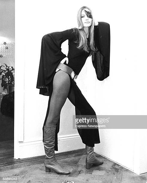 German fashion model Veruschka poses leaning against a wall wearing a thighbaring black dress and a peacock feather over one eye London October 14...