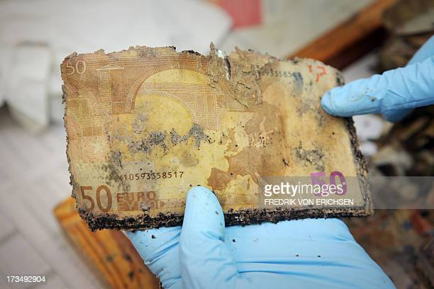 A German Federal Bank employee holds flooddamaged fifty euro banknotes at the counterfeit analysis center in Mainz Germany on July 15 2013 After the...