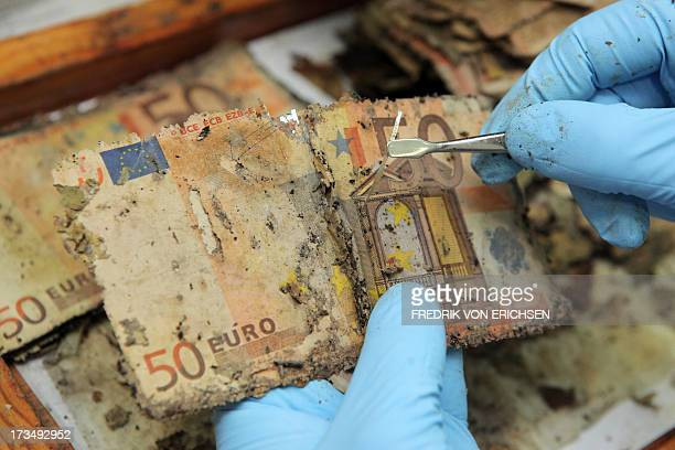 A German Federal Bank employee unravels the safety thread of flooddamaged fifty euro banknotes at the counterfeit analysis center in Mainz Germany on...