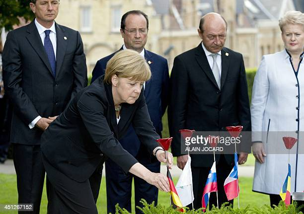 German Federal Chancelor Angela Merkel plants a porcelain flower at the 'Peace bench' ahead of Croatia Prime minister Zoran Milanovic French...