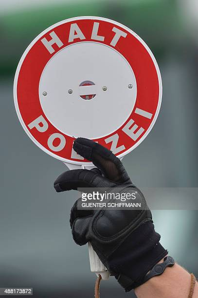 A German Federal Police officer hold a stop sign to control vehicles coming from Austria in Freilassing at the AustrianGerman border on September 14...
