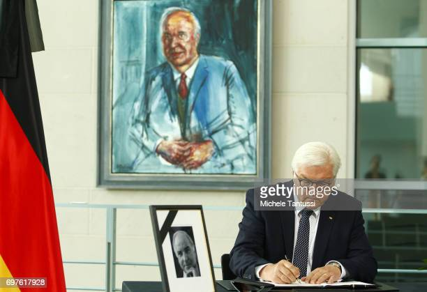 German Federal President FrankWalter Steinmeier signs a book of condolences next to a portrait of late former German Chancellor Helmut Kohl at...