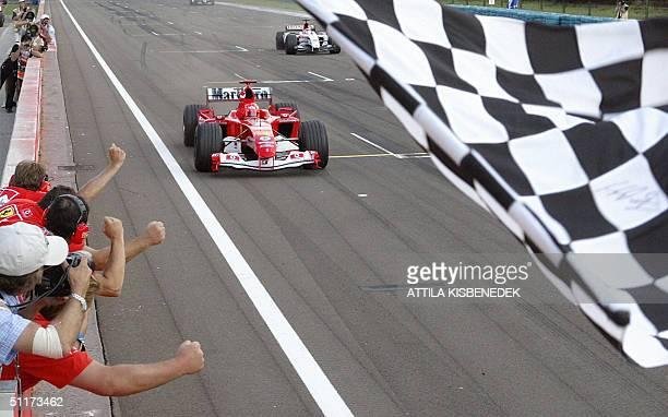German Ferrari driver Michael Schumacher crosses the finish line of the Hungarian Grand Prix 15 August 2004 in Budapest Hungary Michael Schumacher...