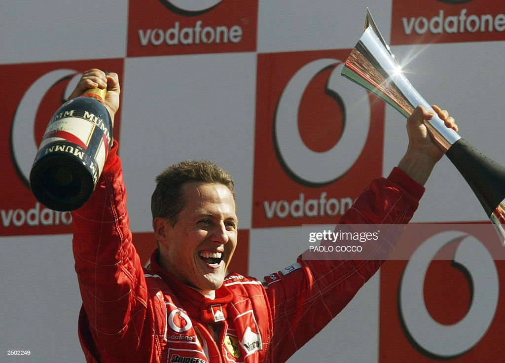 German Ferrari driver <a gi-track='captionPersonalityLinkClicked' href=/galleries/search?phrase=Michael+Schumacher&family=editorial&specificpeople=157602 ng-click='$event.stopPropagation()'>Michael Schumacher</a> holds his trophy on the podium of the Monza racetrack, 14 September 2003, after he won the Italian Formula One Grand Prix. Colombian BMW-Williams driver Juan Pablo Montoya is second and Brazilian Ferrari driver Rubens Barrichello third.