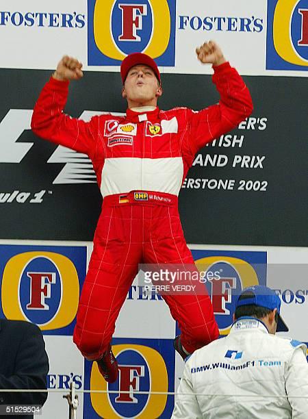 German Ferrari driver Michael Schumacher jumps on the podium of the Silverstone racetrack next to Colombian BMWWilliams driver Juan Pablo Montoya 07...